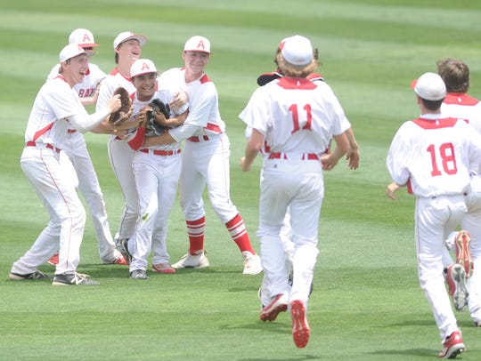 Albany players celebrate with Roman Fuentes in center