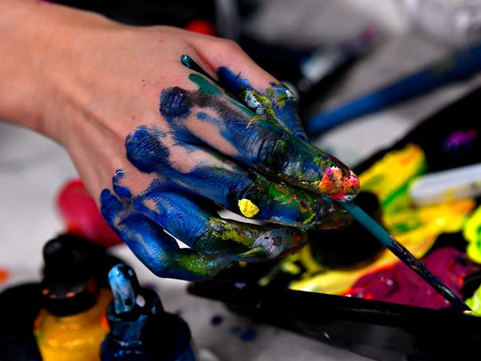 Calina Mishay's hand, covered in paint, dips a brush