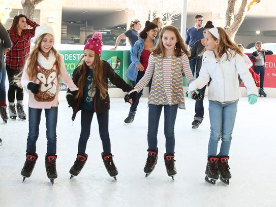 Skaters play on the ice in a seasonal outdoor rink
