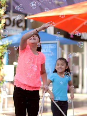 Kids try and capture bubbles during Bubble Bash at Westgate Entertainment District.