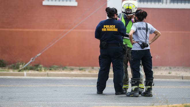 Todd Sanford, assistant chief of the San Angelo Fire Department, center, chats with fire marshals at a scene of a structure fire Saturday, July 7, 2018, at a warehouse at 101 E. 3rd St.