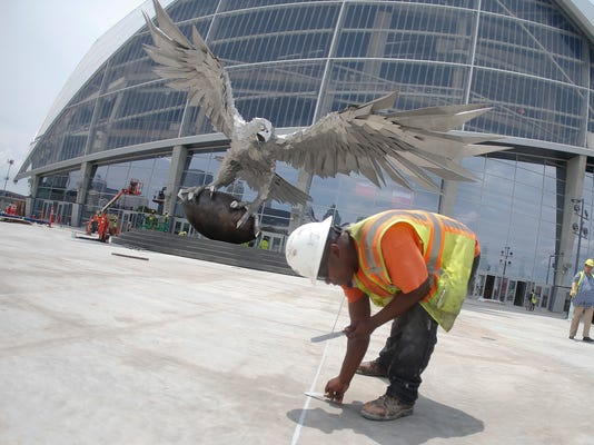 A worker fills cracks in the pavement outside the entrance to the Mercedes Benz Stadium, new home of the Atlanta Falcons football team and the Atlanta United soccer team, Tuesday, July 25, 2017, in Atlanta. (AP Photo/John Bazemore)