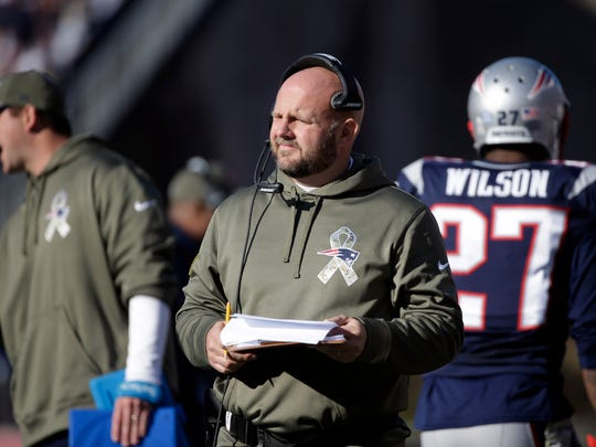 New England Patriots tight end coach Brian Daboll, center, wears military-style clothing during Salute to Service weekend on the sidelines in the first half of an NFL football game against the Detroit Lions, Sunday, Nov. 23, 2014, in Foxborough, Mass. (AP Photo/Steven Senne)