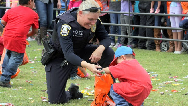 "Deming Police officer Kathleen Schindler helped a young boys scoop up candy during the second annual Great Pumpkin Candy Drop held Saturday, Oct. 22, 2016 at John T. Waits ""Rabbit"" Park on Deming's north side. The candy drop drew more than 1,000 children to enjoy a day at the park, candy treats, hot dogs, chips and cold drinks, - free of cost. The event was sponsored by Friends of the Community, the Deming Police Department and Weaver's Welding out of Las Cruces."