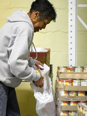 Tri-State Food Bank volunteer, Patricia Hughes loads take home weekend food bags for elementary students Friday, December 2, 2016.