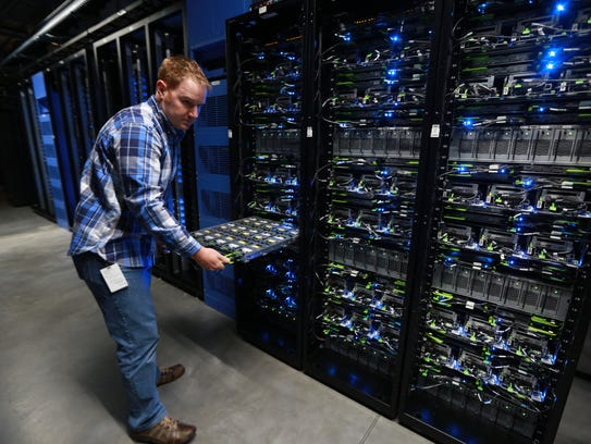 Matt Patterson, a data center technician, opens a drawer