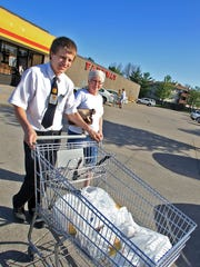 A teenage Fareway employee assists a customer at the