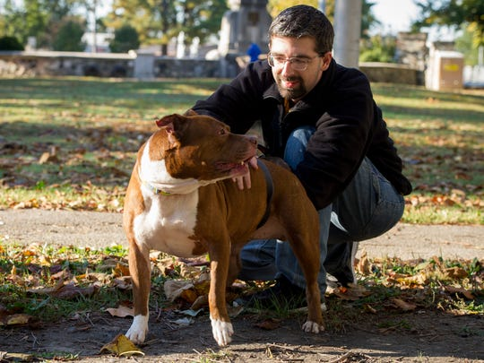 Nathan Shepherd, of Evansville, pets a terrier mix named Red, during Cardio for Canines at Garvin Park in Evansville, Oct. 22. Cardio for Canines takes place every Saturday morning.