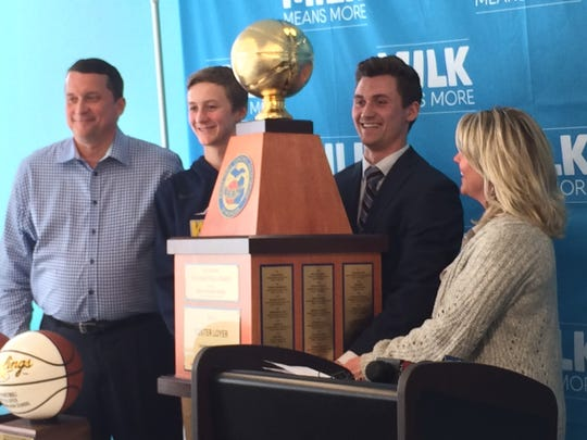 Clarkston guard Foster Loyer (second from right) poses with the Michigan Mr. Basketball trophy and his family on Monday in Detroit.