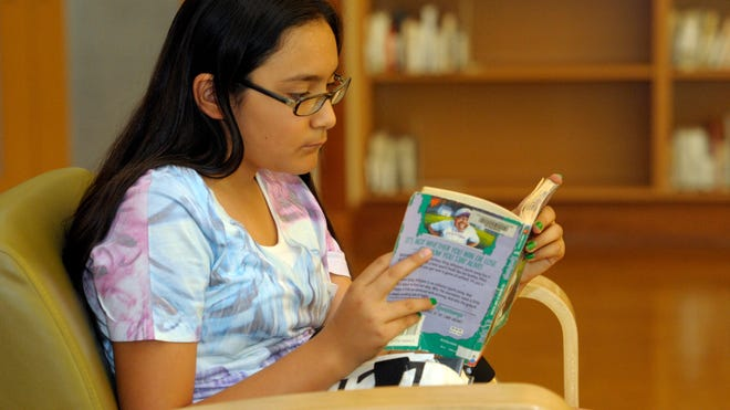 """""""Paws to Read,"""" the Tulare Public Library's summer reading program encourages children and adults to read with prizes offered and runs through July 26. Pictured- Serina Martinez, 12, has already read about 10 books this summer, and plans to read a lot more by the end of summer."""