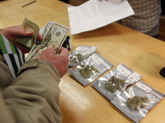 In this Monday, Jan. 1, 2018 file photo, a customer purchases marijuana at the Harborside marijuana dispensary in Oakland, Calif., on the first day that recreational marijuana was sold legally in California. State regulators get credit for taking on the massive job of transforming the longstanding illegal and medicinal marijuana markets into a unified, multibillion-dollar industry, but the results have been mixed. Some companies are doing well, but many others are not.