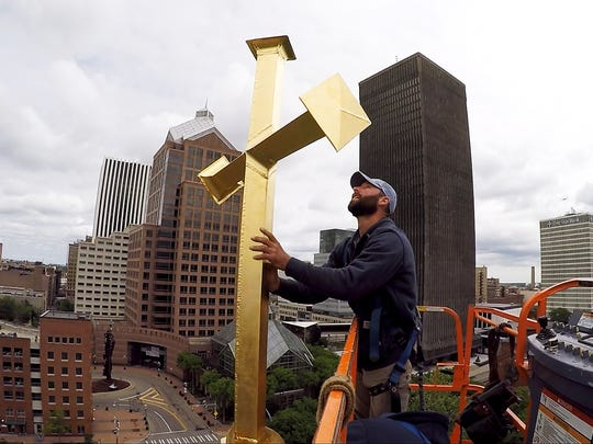 Corey Slye with CSTM Corp. helps attach the new cross placed atop St. Mary's Church to replace the one that was toppled over in the 2017 wind storm.