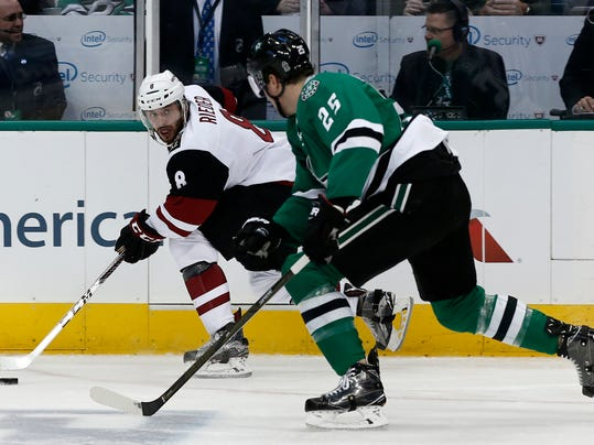 Arizona Coyotes' Tobias Rieder (8) skates the puck up ice on Dallas Stars' Brett Ritchie (25) during the first period of an NHL hockey game, Friday, Feb. 24, 2017, in Dallas. (AP Photo/Mike Stone)