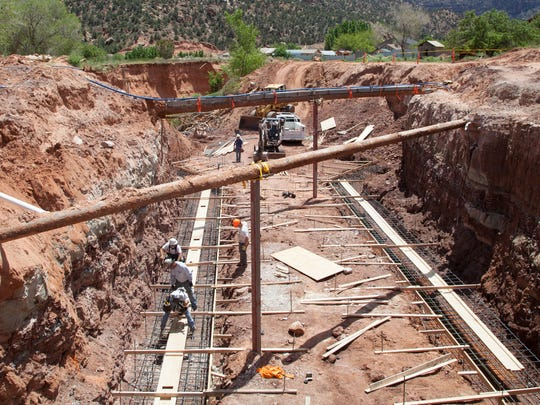 Construction crews begin work Wednesday, May 11, 2016 on a Canyon Street bridge at the site where three women and their children were swept to their death by flash flooding last year in Hildale.