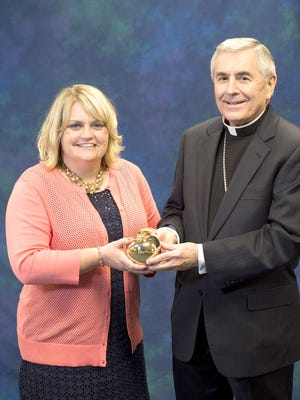Jennifer Noel, left, accepts the Golden Apple Award from Bishop Ronald W. Gainer.