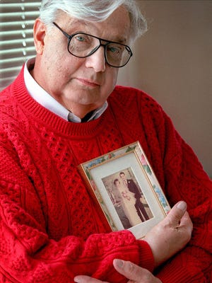 Ray Szmanda holds a wedding day photograph of himself and his late wife, Maxine Ann Szmanda on Dec. 7, 2000. When his wife was diagnosed with cancer in 1998, Ray left his Menards work to care for her.