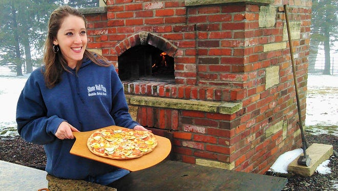 Undaunted by winter cold and fog, Julia McNurlen pulls a fresh, three-cheese garden veggie pizza from the wood-fired brick oven at her farm near Wellman on Friday.