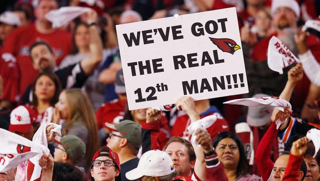 Arizona Cardinals fans cheer for their team as they host the Seattle Seahawks  in their NFL game Sunday, Dec. 21,  2014 in Glendale, Ariz.