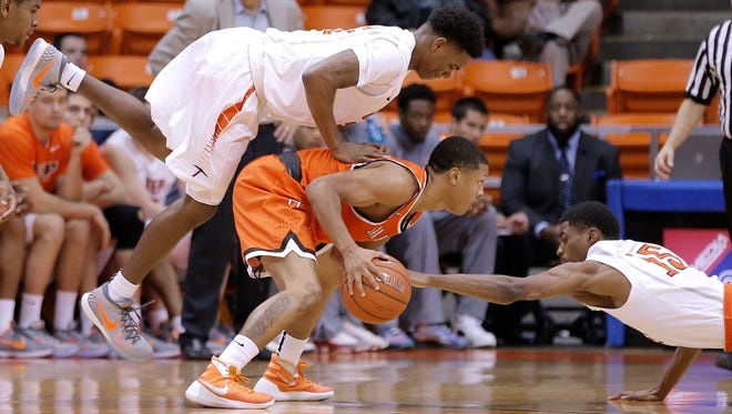 UTEP's Omega Harris, left, tries to avoid landing on Sam Houston State's Jovante' Spivey as UTEP's Tevin Caldwell dives for the steal during the consolation game of the WestStar Bank Don Haskins Sun Bowl Invitational on Tuesday. See more photos at elpasotimes.com.