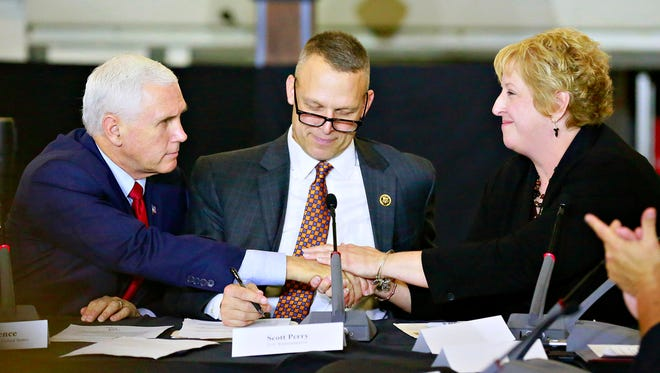 Vice President Mike Pence, left, reaches across U.S. Representative Scott Perry to shake hands with small business Co-owner of The Camera Box Tammy Shearer, right, during a round table discussion at Military & Commercial Fasteners Corporation in Manchester Township, Saturday, Nov. 4, 2017. Dawn J. Sagert photo
