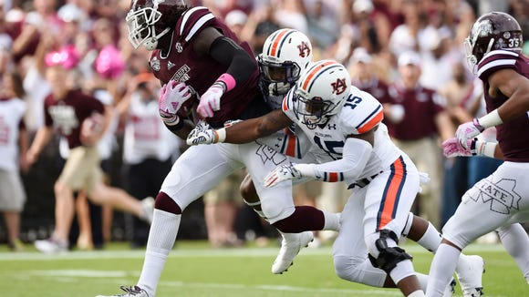 Oct 11, 2014; Starkville, MS, USA; Mississippi State Bulldogs wide receiver De'Runnya Wilson (1) carries for a touchdown on a reception against Auburn Tigers defensive back Joshua Holsey (15) and defensive back Jonathan Jones (3) during the first quarter at Davis Wade Stadium. Mandatory Credit: John David Mercer-USA TODAY Sports