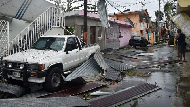 Residents of San Juan, Puerto Rico, deal with damages to their homes on September 20, 2017, as Hurricane Maria batters the island.