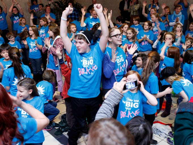 """Bradley Powell, left, and Phoebe Cornell sing and dance along with other students, teachers and parents of Community Montessori as they participate in a Flash Mob to the song """"Brave"""" inside Green Tree Mall. The school is producing a video to encourage """"not just children to become BRAVE, but schools being brave and not focusing all of their time on teaching to a test."""" Dec. 12, 2013"""