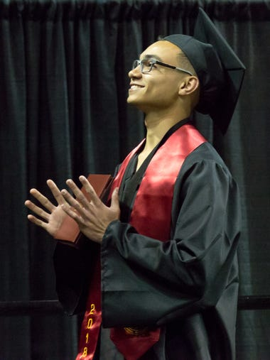 Devynn Davis holds his diploma and looks up at his