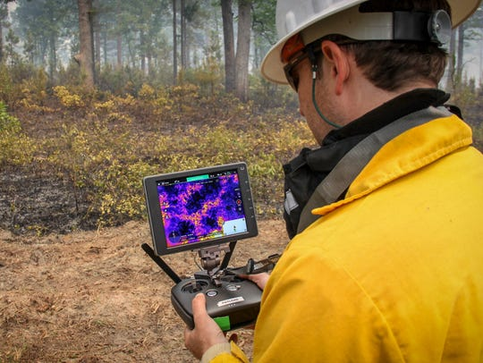 A drone pilot views the infrared camera output during