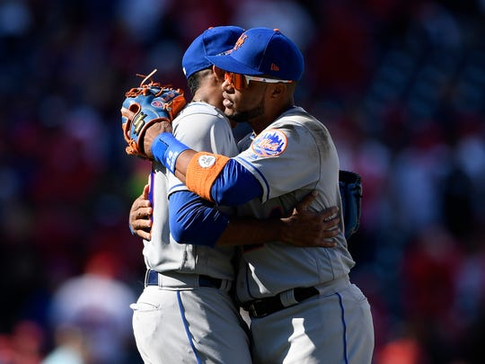 New York Mets' Robinson Cano, right, hugs relief pitcher Edwin Diaz, left, after a baseball game against the Washington Nationals, Thursday, March 28, 2019, in Washington. The Mets won 2-0. (AP Photo/Nick Wass)