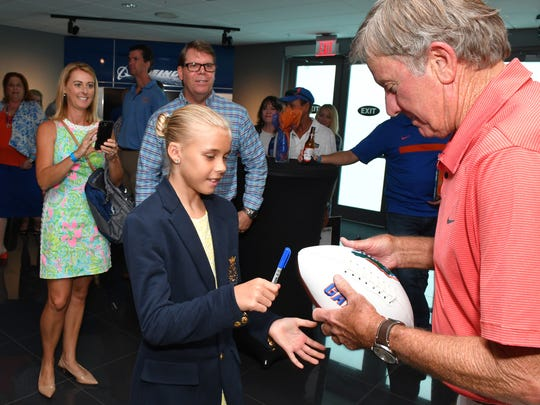 Grace Vevera, 10, meets legendary football coach Steve Spurrier, the winningest coach in Florida football history, at the Space Coast Gator Club's annual Gator Gathering at the Kennedy Space Center Visitor Complex.