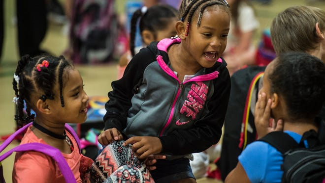 Children mingle in the Fairview Elementary gymnasium before the start of their first day of school on Wednesday, Aug. 9, 2017 in Richmond, Ind.