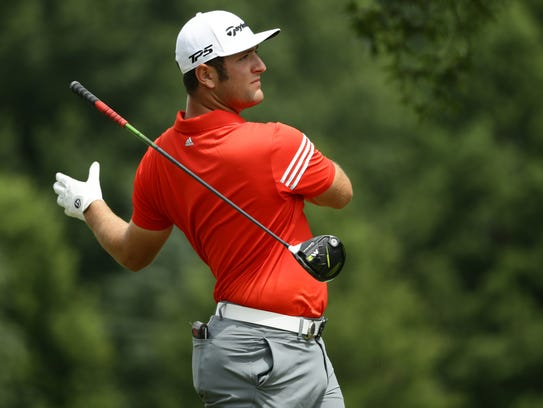Jon Rahm reacts to his drive on the 10th hole during