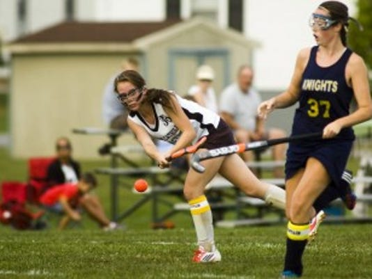 Delone Catholic's Hannah Stambaugh passes to a teammate as Eastern York's Sydney Deitzel watches during Thursday's field hockey game at Delone Catholic. The Golden Knights won, 2-1. (The Evening Sun - Shane Dunlap)