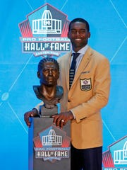 Former NFL player Randy Moss poses with a bust of himself
