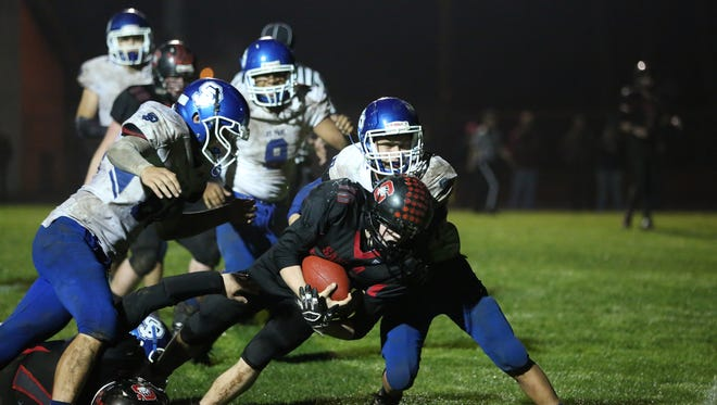St. Paul defenders surround Santiam's Trevor Tinney as the Buckaroos defeat Santiam 29-27 in a Tri-River Conference game on Friday, Oct. 7, 2016, at Santiam High School in Mill City.