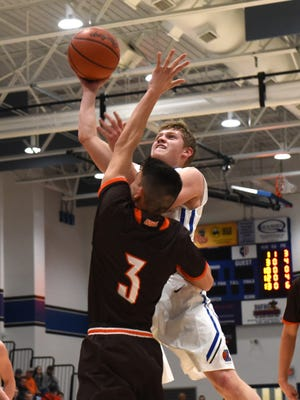 Zanesville's Colton Foreman goes over Meadowbrook's Trey Singleton for a shot in the Blue Devils' 59-51 loss on Tuesday.