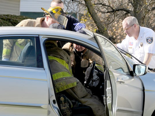 Emergency workers try to coax a man out of his car Wednesday after he crashed into a  home at 619 Bowman Street.