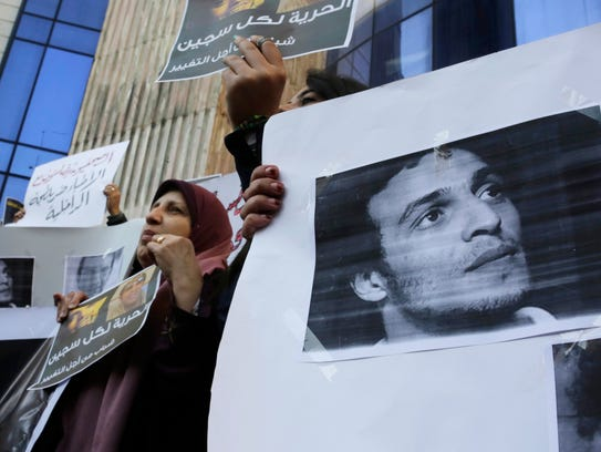 Egyptian journalists hold posters calling for the release
