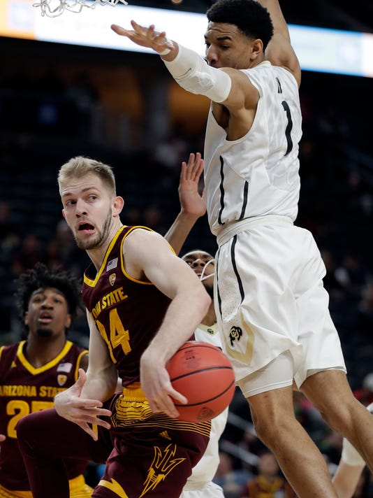 Arizona State's Kodi Justice passes under Colorado's Tyler Bey during the first half of an NCAA college basketball game in the first round of the Pac-12 men's tournament Wednesday, March 7, 2018, in Las Vegas. (AP Photo/Isaac Brekken)