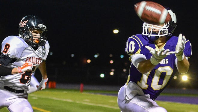 Waukee's receiver Koy Schneiter (10) reaches out for a pass as he's trailed by Sioux City East's Grayson Brower (8) during the first half of the playoff game at Waukee Stadium on Wednesday, Oct. 29, 2014.
