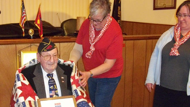Arlene Myslinski, of Mountain Home Quilts of Valor, presented Charles Jackson with a Quilt of Valor recently at the American Legion Post 52. Jackson is a WWII veteran of the US Navy.  Lisa Gunter, right, is a member of Mountain Home Quilts of Valor, a veteran, and member of the American Legion.