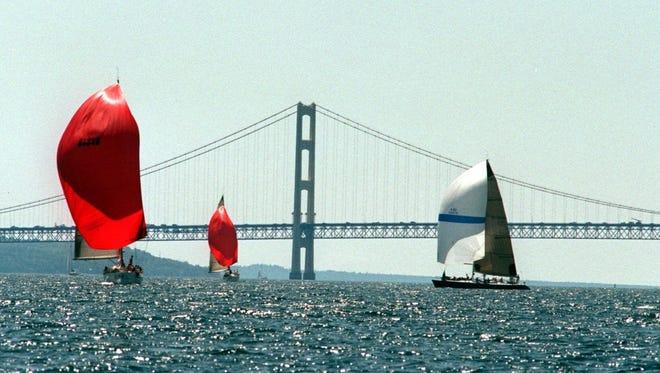 Yachts pass the Mackinac Bridge for the annual Chicago to Mackinac Island race on Lake Michigan.