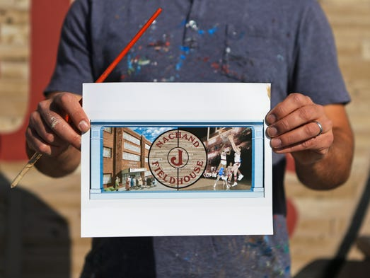 Artist Jeremy Jarvis holds a rendering of what the