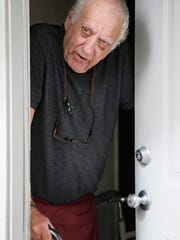 Stephen Schmauss leans on his walker and his cane as he talks at the front door of his home in Tulsa, Okla., Friday, Aug. 19, 2016. Schmauss' husband, Stanley Majors, is accused in the murder of neighbor Khalid Jabara. (AP Photo/Sue Ogrocki)
