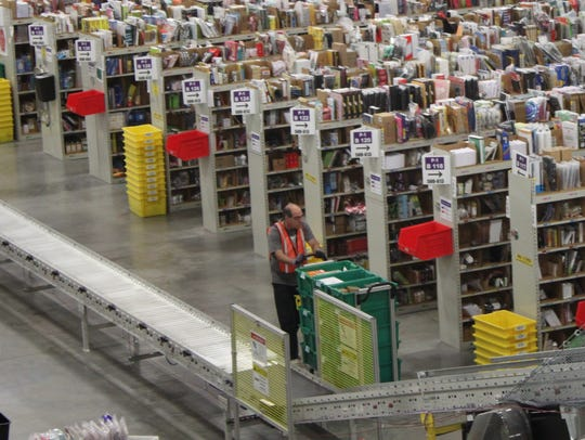A worker pushes a cart in the Amazon Fulfillment Center