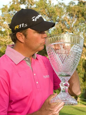 Bo Van Pelt kisses the trophy after winning the Perth International golf tournament in Perth on Oct. 21, 2012.