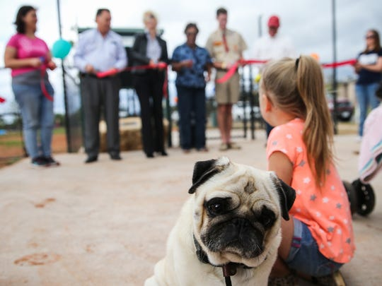 Dog owners with their dogs gather to for the ribbon cutting ceremony at the grand opening of the dog park Saturday, Oct. 21, 2017, along the Red Arroyo Trail.