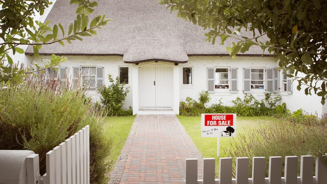 House with for sale sign on the front lawn.
