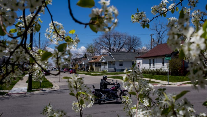 A motorcyclist rides through the intersection of Francis and 16th streets Thursday, May 5, 2016 in Port Huron's Harrison Pointe neighborhood. The City of Port Huron has demolished 42 blighted homes in the neighborhood since 2009- an investment of about $450,000.
